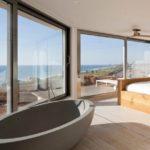 Спальня и ванна в одном помещении с большими окнами