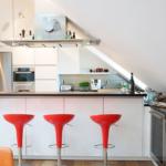 Кухня на мансарде с красными барными стульями